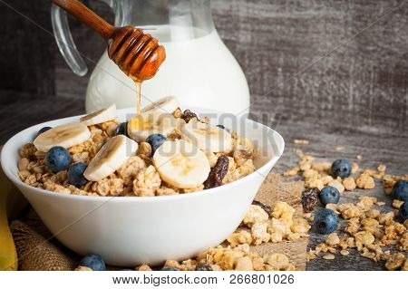 Healthy breakfast concept with oat flakes and fresh berries on rustic background. Food made of granola and muesli. Healthy banana smoothie with blackberries, honey and milk. stock photo