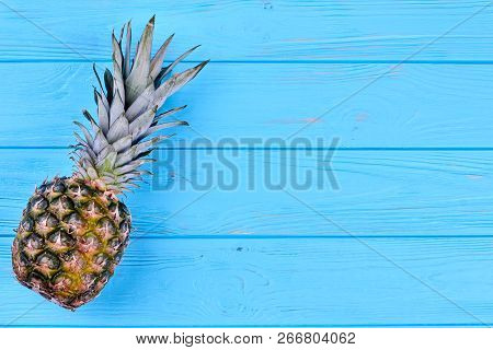 Ripe delicious pineapple and copy space. Whole hawaiian pineapple fruit on blue wooden table with text space. Health benefits of pineapple. stock photo