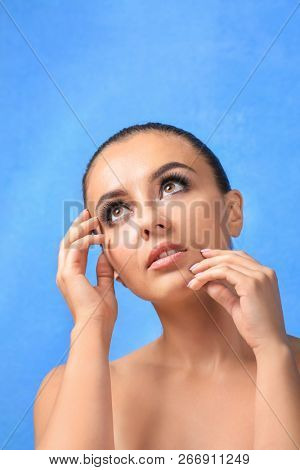 Beautiful young woman with eyelash extensions on color background stock photo