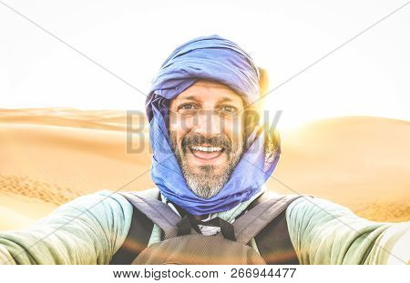 Young man solo traveler taking selfie at Erg Chebbi desert dune near Merzouga in Morocco - Adventure wanderlust concept on world famous nature wonder in Maroc - Warm bright sunset color filtered tones stock photo