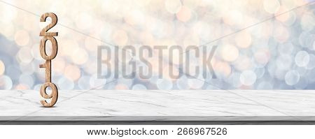 Happy new year 2019 (3d rendering wood texture) on white marble table at soft pastel blue and orange sparkle bokeh light abstract background,mock up banner space for holiday greeting card stock photo