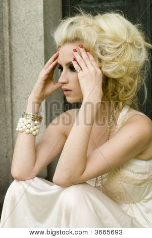 Woman with blonde hair wearing red nail polish and a cream dress stock photo