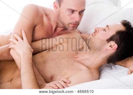Happy homo couple in a white bed taking care of his boyfriend stock photo