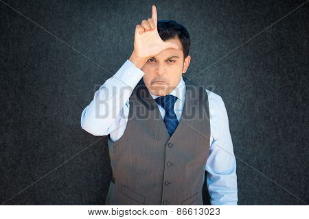 Closeup portrait funny young man in vest and tie displaying loser sign on forehead looking at you with disgust isolated gray black background. stock photo