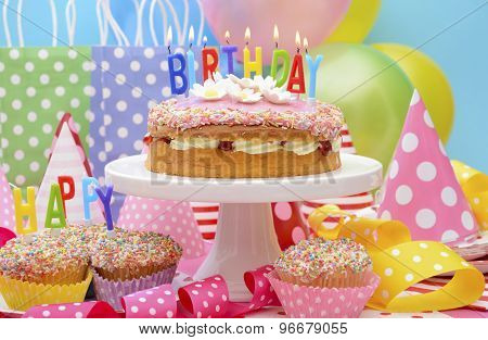 Bright colorful Happy Birthday Party Table with balloons streamers party favor gift bags and birthday cake with lit candles. stock photo