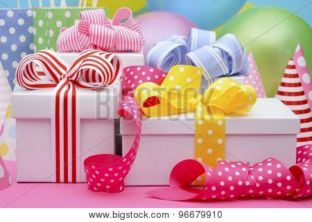 Bright colorful party table with balloons streamers party favor gift bags and gifts with bright color ribbons and bows. ** Note: Shallow depth of field stock photo