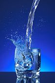 Water sprinkle filled a glass, blue foundation, invigorating, freshness and wellbeing. Water bottle,