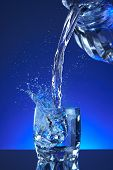 Water sprinkle filled a glass, blue foundation, reviving, freshness and wellbeing. Water bottle,