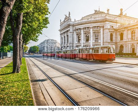Famous Wiener Ringstrasse with historic Burgtheater (Imperial Court Theatre) and traditional red electric tram at sunrise with retro vintage Instagram style filter effect in Vienna Austria stock photo