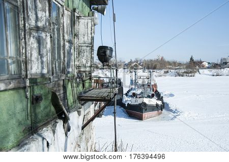 The old riverboat is frozen on the ice stock photo