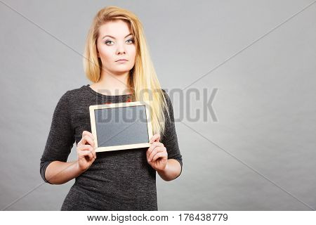 Attractive blonde having serious face expression holding black blank board for copyspace or textspace studio shot on grey background. stock photo