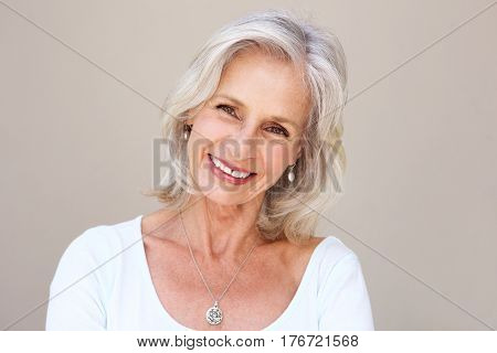 Beautiful Older Woman Smiling And Standing By Wall