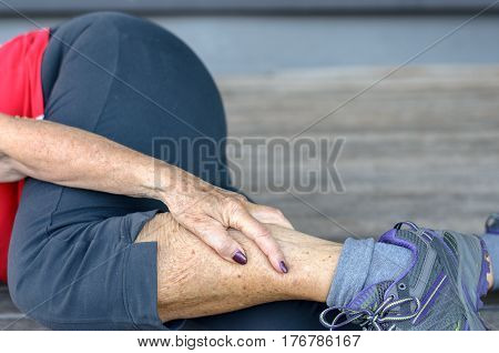 Fit sporty senior woman suffering from lower leg cramps during a workout clutching her calf in pain close up view of her lower body lying on a wooden floor or deck stock photo