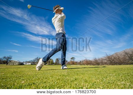 Wide angle view of a golfer teeing off from a golf tee on a bright sunny day on a golf course in south africa. stock photo