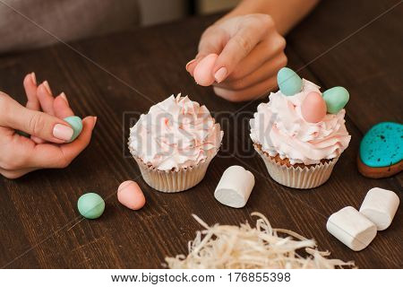 Masterclass of preparing decorated cupcakes with white cream on wooden table. Cookery arts. Easter gift, small business, delivery of sweets, craftmanship concept stock photo