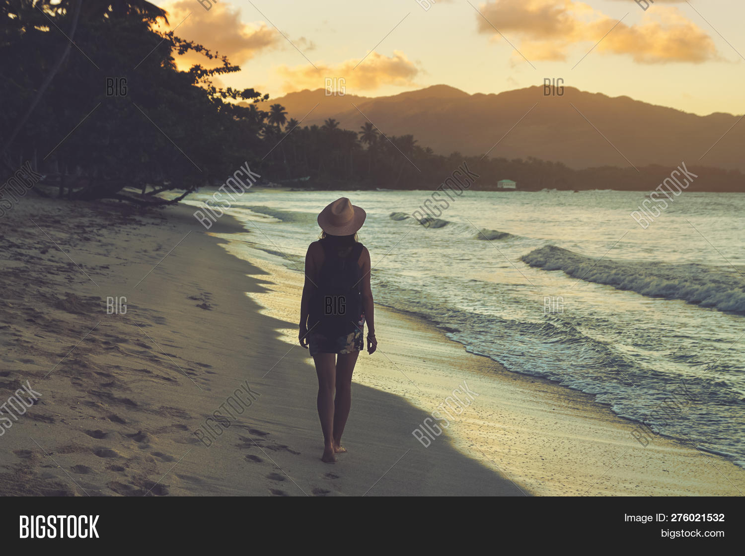 Traveler Girl Walking On Tropical Beach In Sunset. Vintage Photo Of Young Girl Traveler In Vacation.