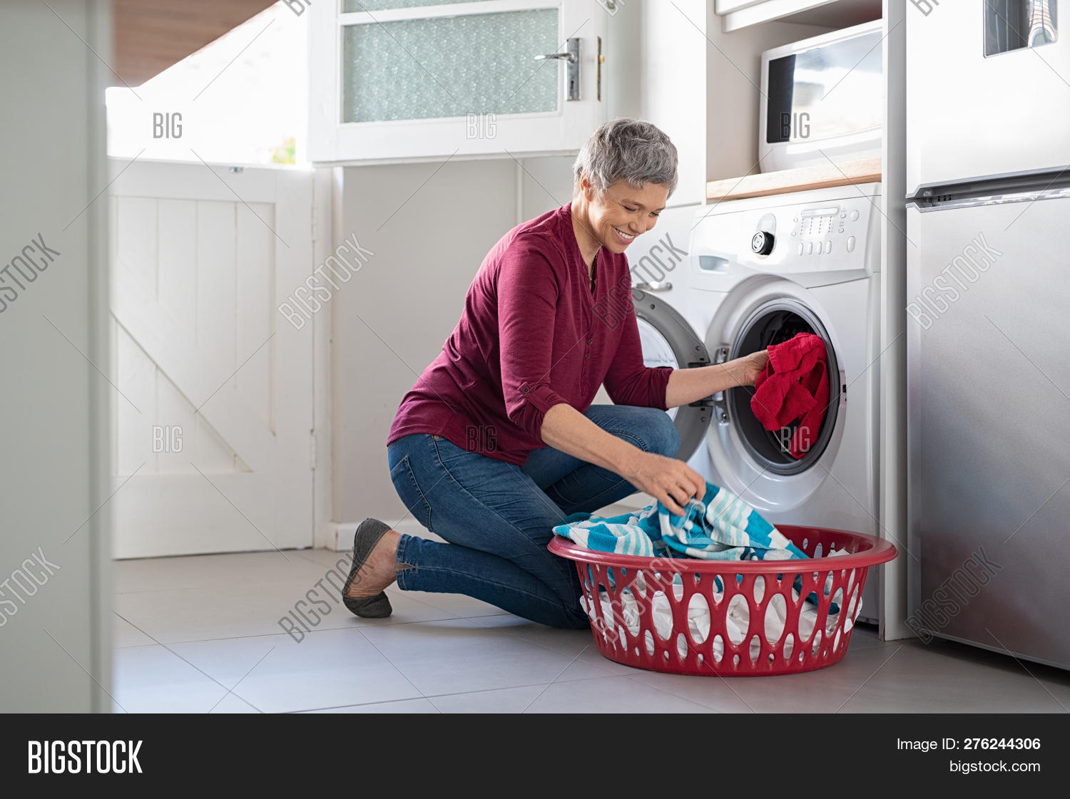 50s,60s,appliance,basket,casual,chores,clean,cloth,clothes,clothing,crouching,daily,dirty,dirty clothes,dryer,gray hair,happy,home,house work,household,housekeeper,housekeeping,housewife,housework,hygiene,indoors,kneeling,laundering,laundry,laundry basket,loading,machine,mature,matured,mid adult woman,middle aged woman,old woman,people,putting,routine,senior,senior woman,smile,toothy smile,washer,washing,washing machine,wife,work