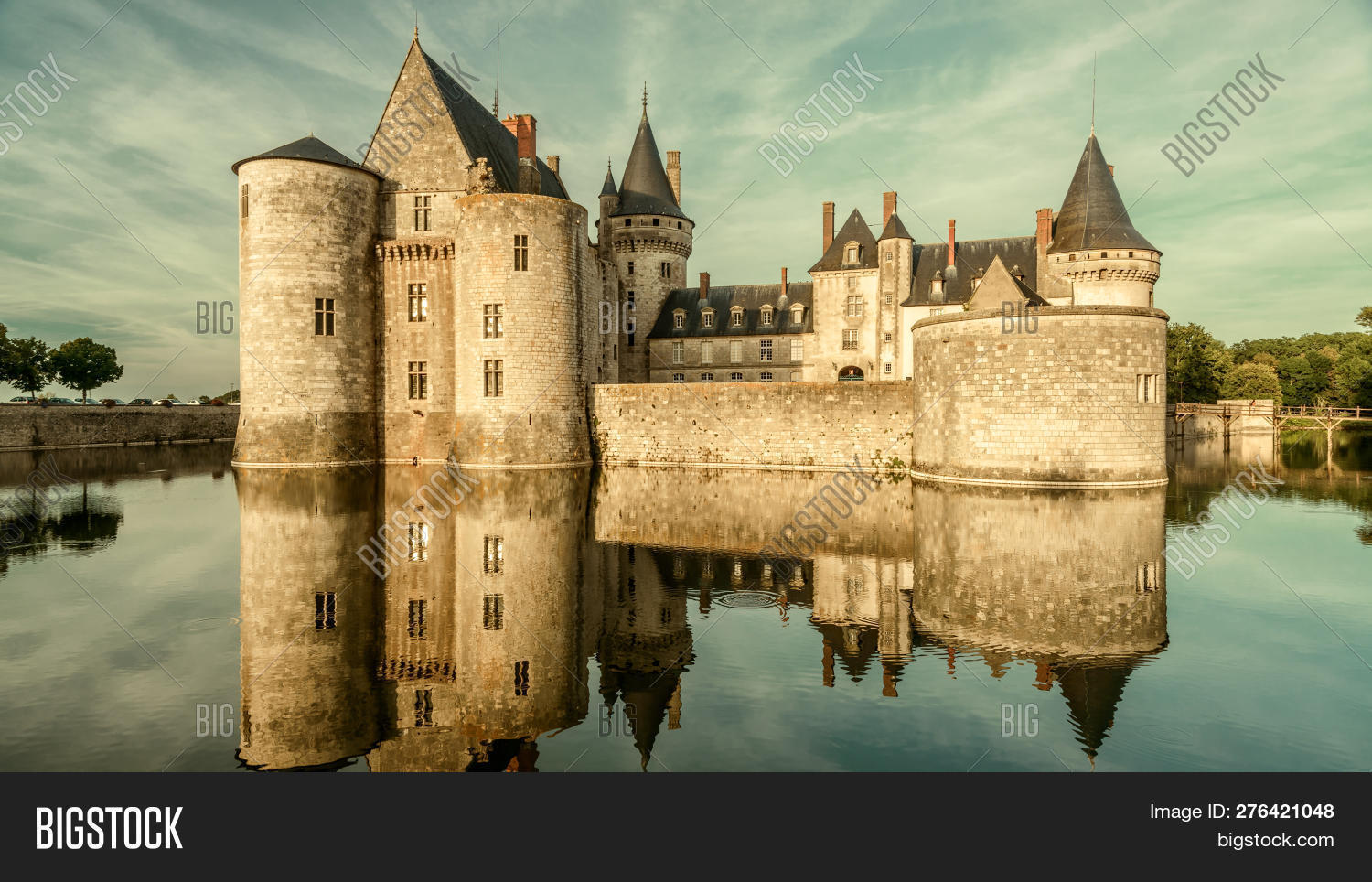 Castle or chateau de Sully-sur-Loire in sunset light, France. This old castle is a famous landmark of Loire Valley. Panorama of the medieval castle on the river. French vintage castle in evening.