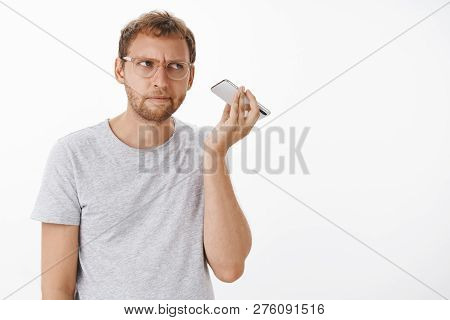 Guy listening audio message cannot understand what strange noise coming from dynamics holding smartphone near ear staring aside with intense focused expression concentrating on sound stock photo