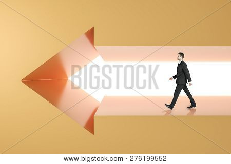 Side view of young businessman walking in arrow wall. Success and career concept. stock photo