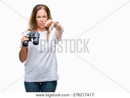 Middle age hispanic woman looking through binoculars over isolated background with angry face, negative sign showing dislike with thumbs down, rejection concept stock photo