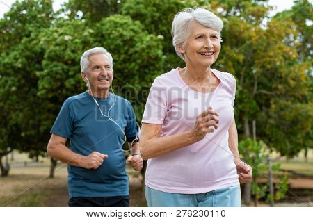 Senior couple running outside at park. Elderly man and old woman jogging together. Retired man and a