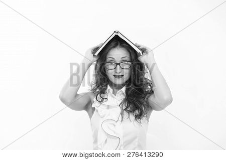 Woman with long hair white blouse hold book as roof. Teacher with glasses looks attractive. Seductive office administrator. Pressure of to do list. Lady strict teacher or seductive office manager. stock photo