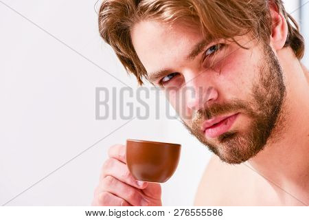 Best time to have your cup of coffee. Guy attractive appearance man enjoy hot fresh brewed coffee close up. First sip. Every morning with his coffee. Man bearded handsome macho hold cup of coffee. stock photo