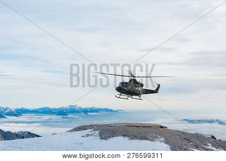 Mountain rescue helicopter landing to pick up wounded. stock photo