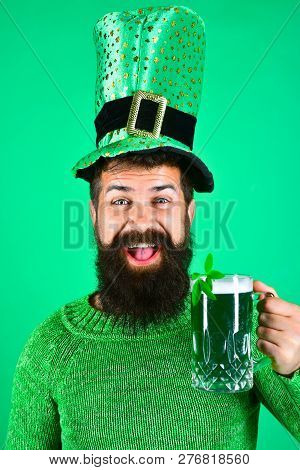 St. Patricks Day. Bearded man in leprechaun hat. Portrait of smiling man with green beer. Bearded leprechaun. Happy Irish leprechaun with black beard. Bearded man. Green background. Irish tradition. stock photo