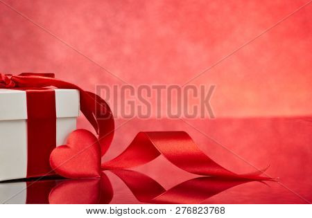 Gift box and red satin heart on a red background. Valentine\'s Day card with copy space. Design eleme