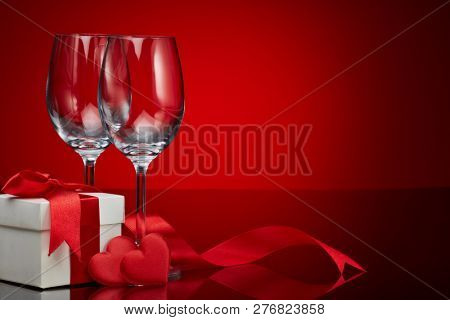 Gift box, red satin hearts and two empty wineglasses on a red background. Valentine\'s Day card with