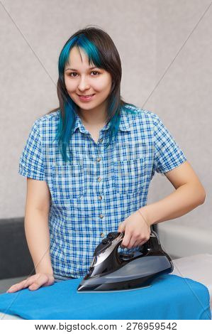 Young cheerful woman ironing clothes in home interior stock photo