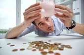 business, individuals, funds, emergency and cash sparing idea - businessperson shaking piggy bank an