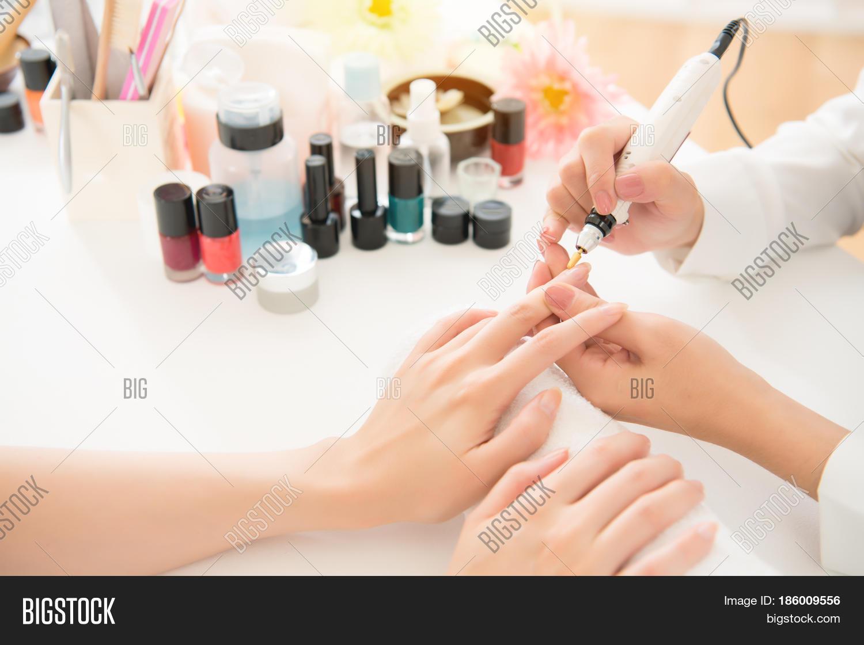 female asian salon manicurist using portable pen shape electric nail drill art salon manicure file pedicure tool polish buffing for her customer