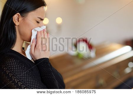 burial, people, grief and mourning concept - close up of sad woman with paper wipe crying near coffin at funeral in church stock photo