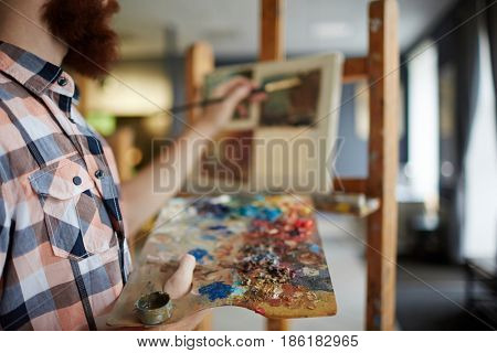 Closeup portrait of modern bearded artist painting picture on canvas using palette with canvas in ar