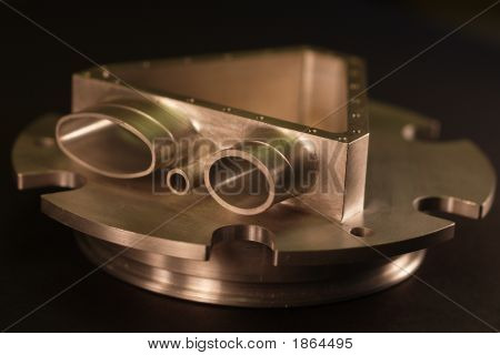This is a picture of a custom milled or machined part. Machine shops use manufacture these types of custom parts with CNC machines lathes mills and turning centers. stock photo
