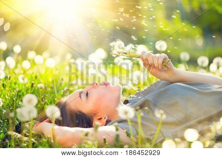 Beautiful Young Woman lying on the field in green grass and blowing dandelion. Outdoors. Enjoy Natur