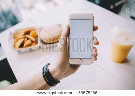 Young man\'s hand holding mobile phone. He is sitting in cafe and having his meal while searching for some information. Place for your advert or logo. Close up. Horizontal position of the phone