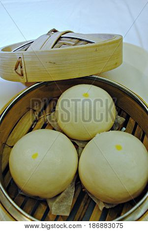 Siopao or steamed buns in a bamboo steamer Siopao is a popular food in southeast Asia usually filled with meat and steamed. stock photo