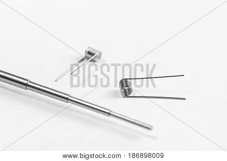 A simple Clapton coil two pieces and Micro Coil Jig on a white background isolated stock photo