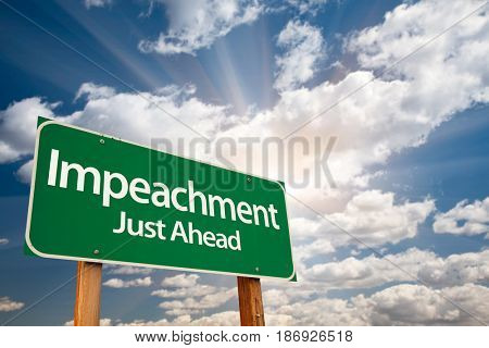 Impeachment Green Road Sign with Dramatic Clouds and Sky stock photo