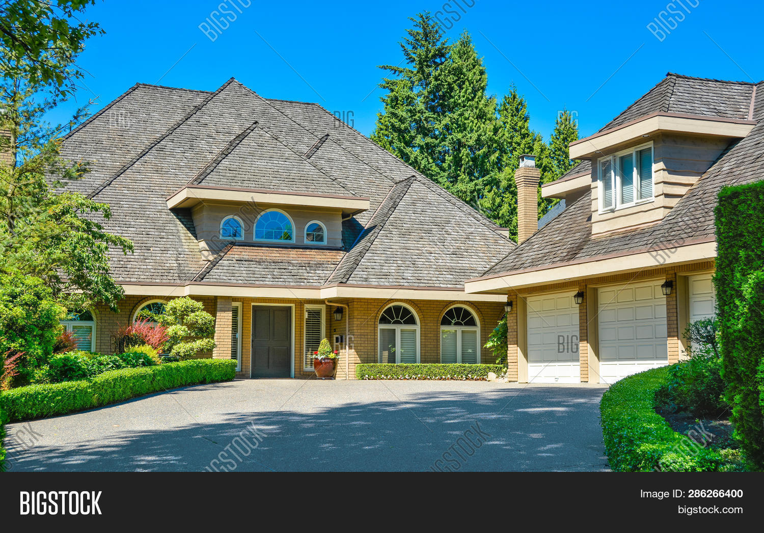 Residential House With Massive Roofs With Green Hedge At The Entrance On Blue Sky Background. Family