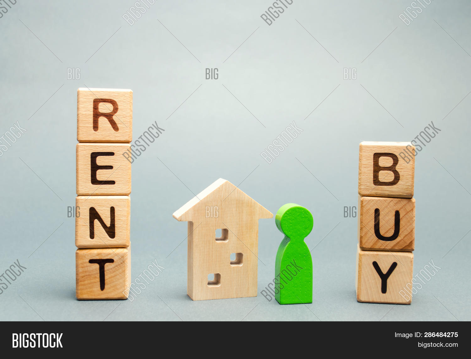 Wooden Blocks With The Word Rent Or Buy And A Person Stands Near The House. Make The Right Decision.