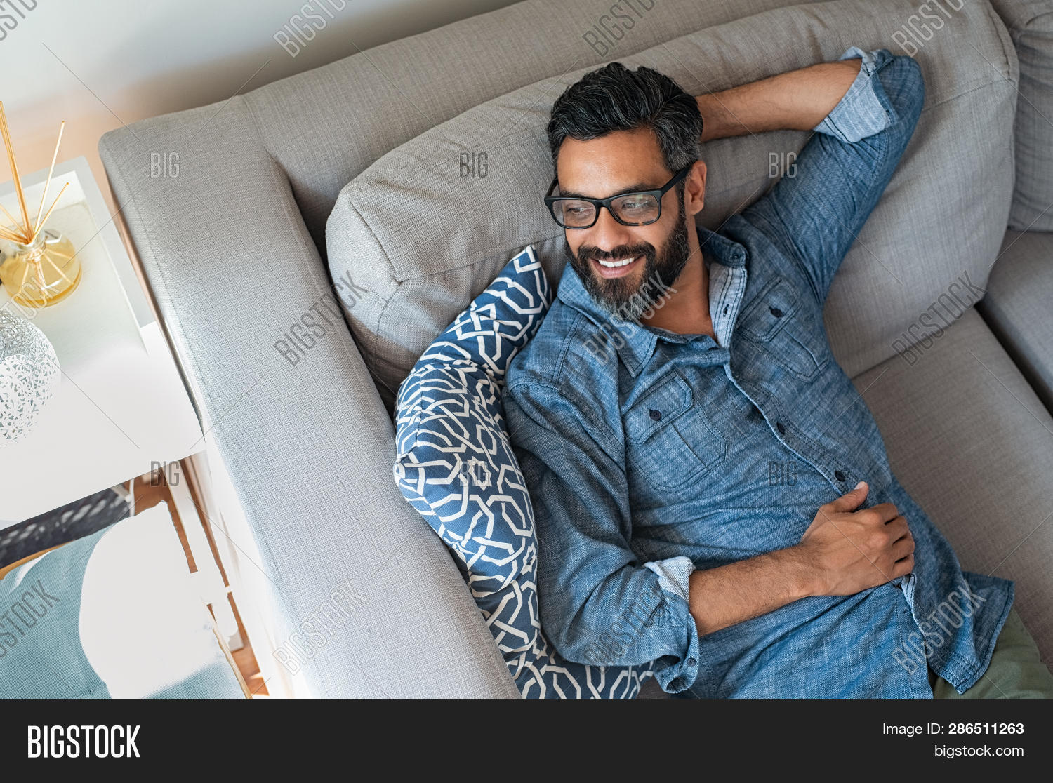 Mature man resting on sofa and thinking about the future. Hispanic man lying on couch and looking aw