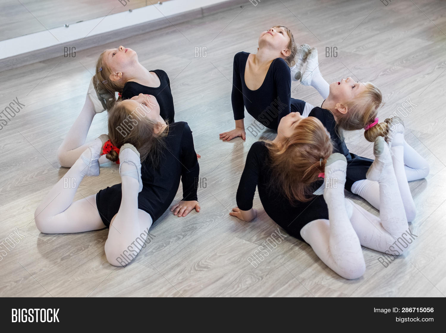 Little girls do gymnastics in a dance class. The concept of sport, education, childhood, hobbies and dance