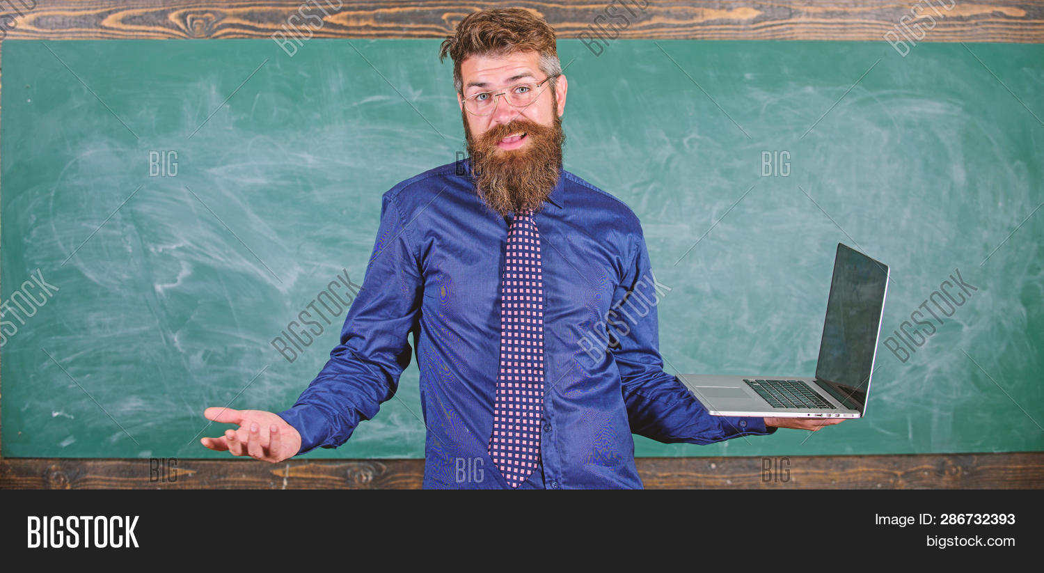 Teaching issues using modern technologies. Hipster teacher confused expression holds laptop. Teacher bearded man confused work with modern laptop chalkboard background. Distance education issues