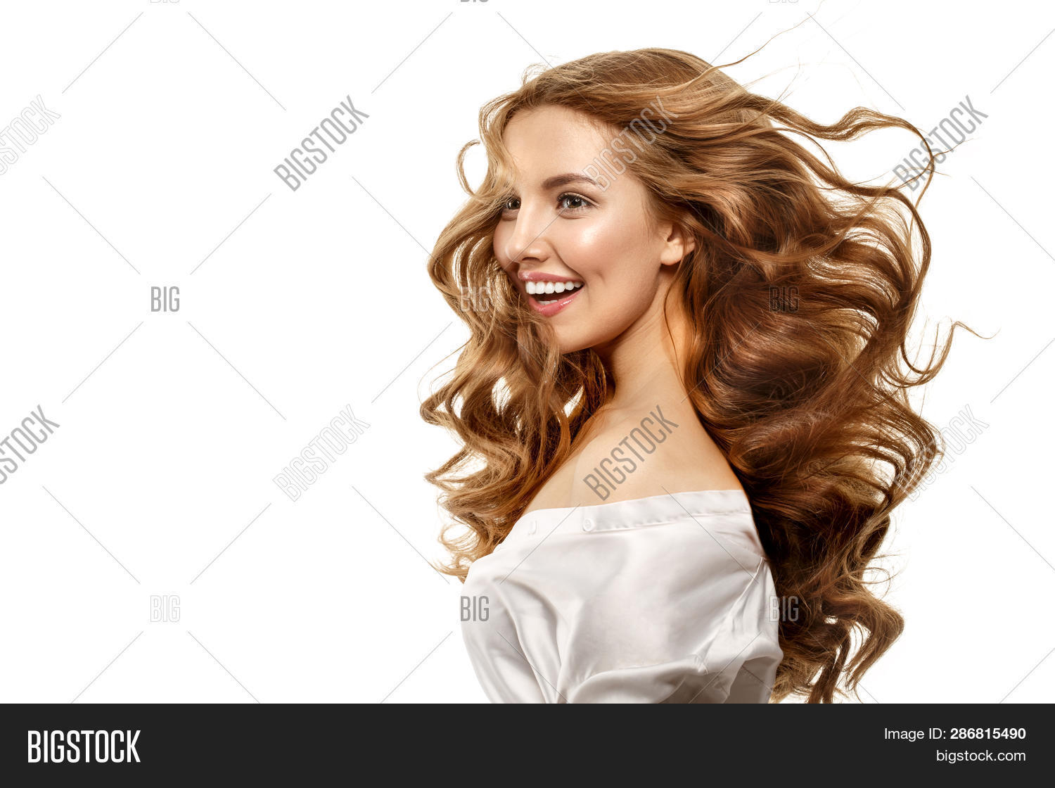 Portrait of beautiful girl with smiley face. Model laughing looking at camera. Flying curly hair. Ha