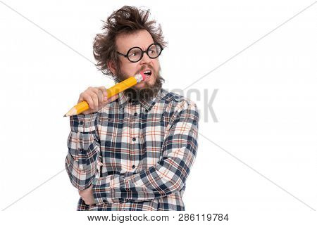 Crazy thoughtful bearded Man in plaid shirt with funny Haircut in eye Glasses holding Big Pencil - ponder and dreaming, isolated on white background. stock photo